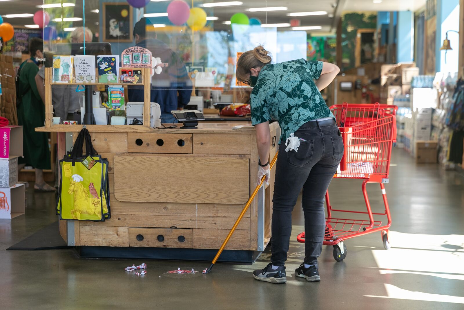 A Trader Joe's manager scrapes the 6-foot distance stickers off the floor on June 15, 2021. Credit: Kelly Sullivan