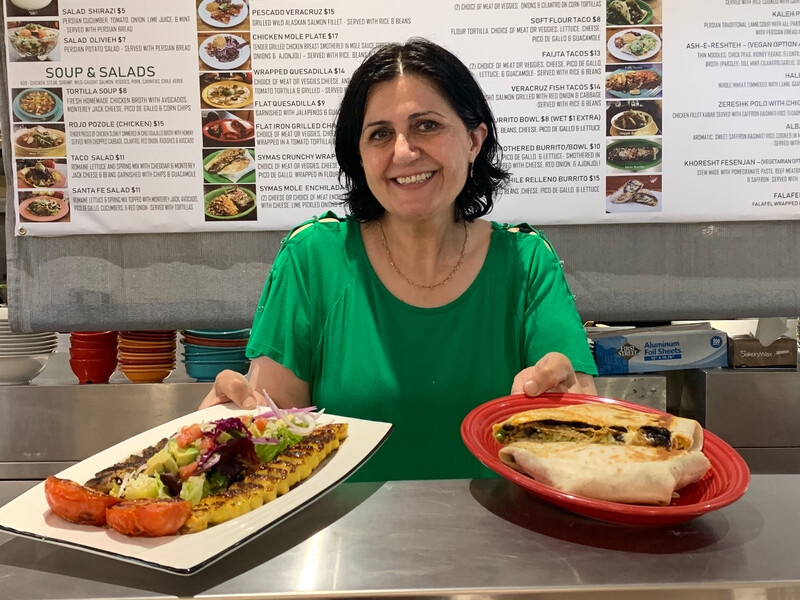 Owner Sima Dehestani has added Persian food to the menu at Syma's Grill. Here, she holds dishes representing food from both cultures: koobideh with Santa Fe salad (left) and Syma's Crunchy Wrap (right). Credit: Anna Mindess