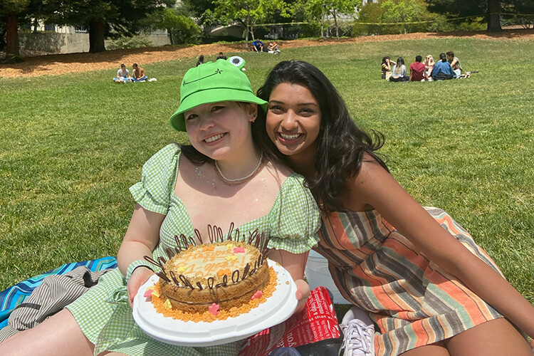 Connect-in-Place co-founders Danielle Egan (left) and Saumya Goyal celebrate the first anniversary of their startup on Memorial Glade with a cake made by Egan. Credit: Victoria Brendel