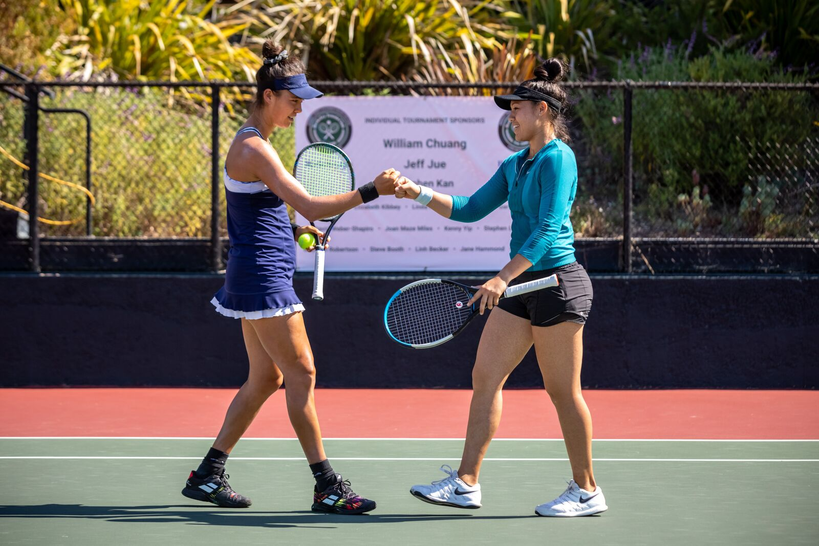Sophie Chang and Angela Kulikov fist bump after a successful play at the Berkeley Tennis Club Women's Challenge tournament on October 3, 2021. Credit: Kelly Sullivan