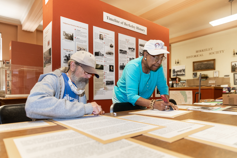 """Harvey Smith and Dr. Stephanie Johnson,  co-curators of the  """"African Americans in Berkeley"""" exhibit, make preparations   before the opening of the second leg of the three-part series, which opens on Sunday, May 16, 2021."""
