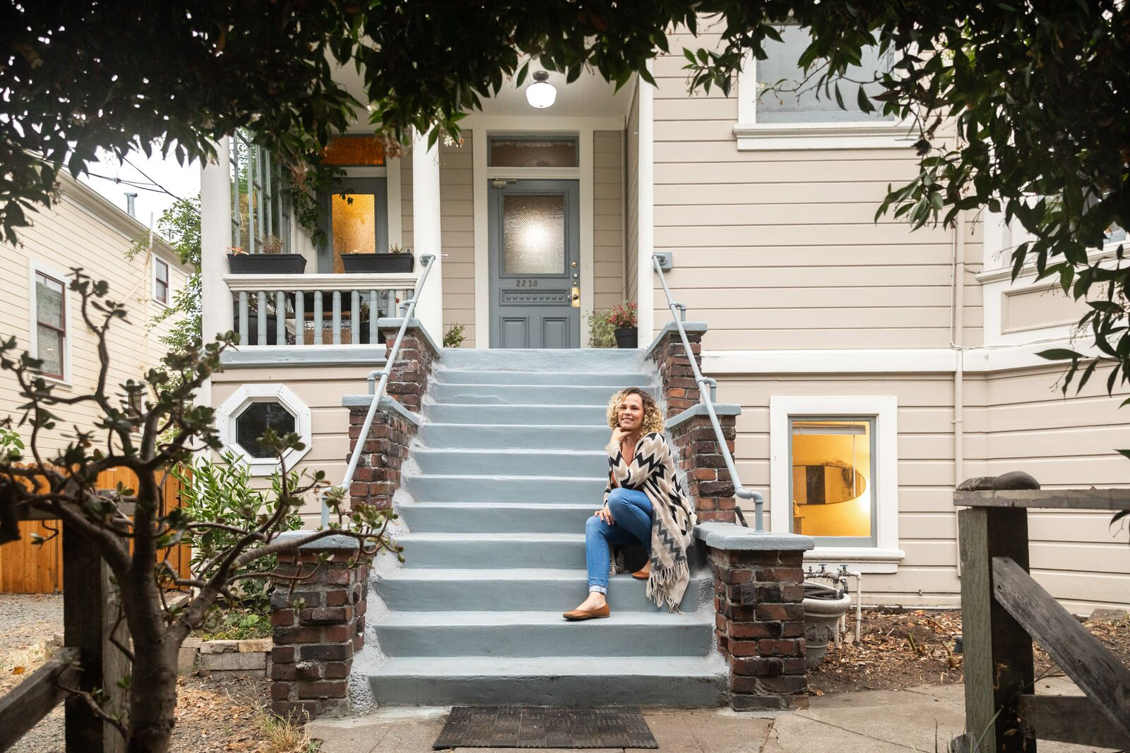 Kimberly Jean, who grew up in the house at 2228 McKinley Ave., poses for a photo on the front steps, on August 20, 2021. Credit: Kelly Sullivan