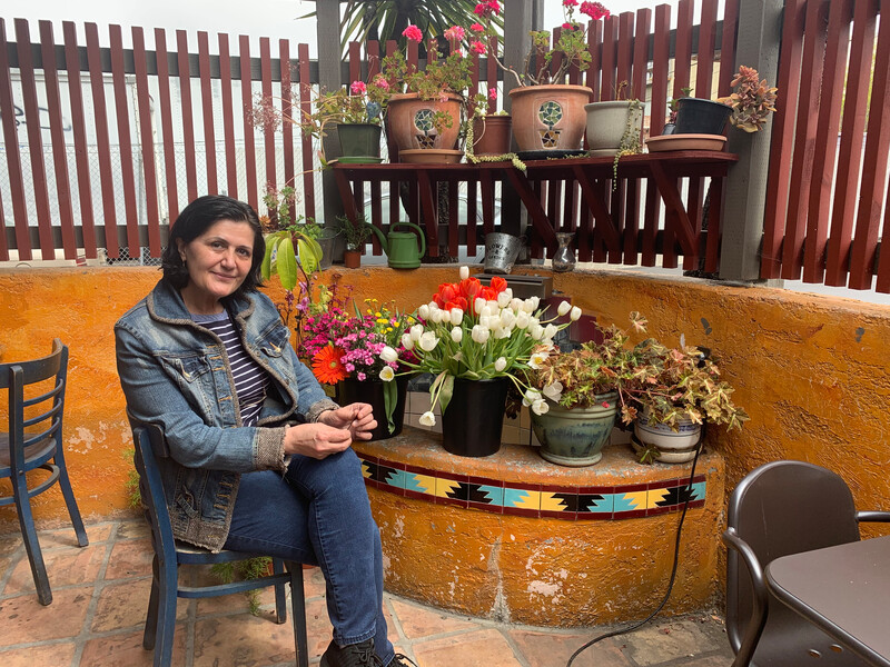 Syma's Grill owner Sima Dehestani sits on the restaurant's back patio. Credit: Anna Mindess