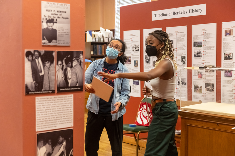 """Mimia Ousilas (from left) and Luce Collymore Abbas,  curatorial assistants of the  """"African Americans in Berkeley"""" exhibit, make preparations before the opening of the second leg of the three-part series, which opens on Sunday, May 16, 2021."""