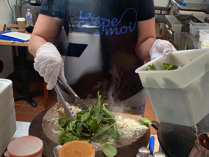 Rebecca Dahmani adds fresh spinach to a savory crepe. Photo: Anna Mindess