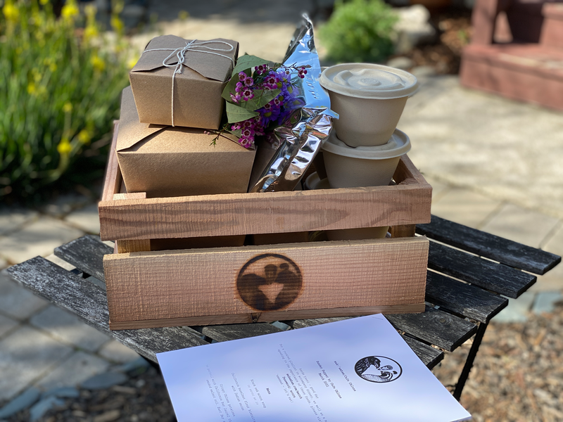A wooden crate filled with takeout boxes and food containers along with a bouquet of flowers sits on a table outside.