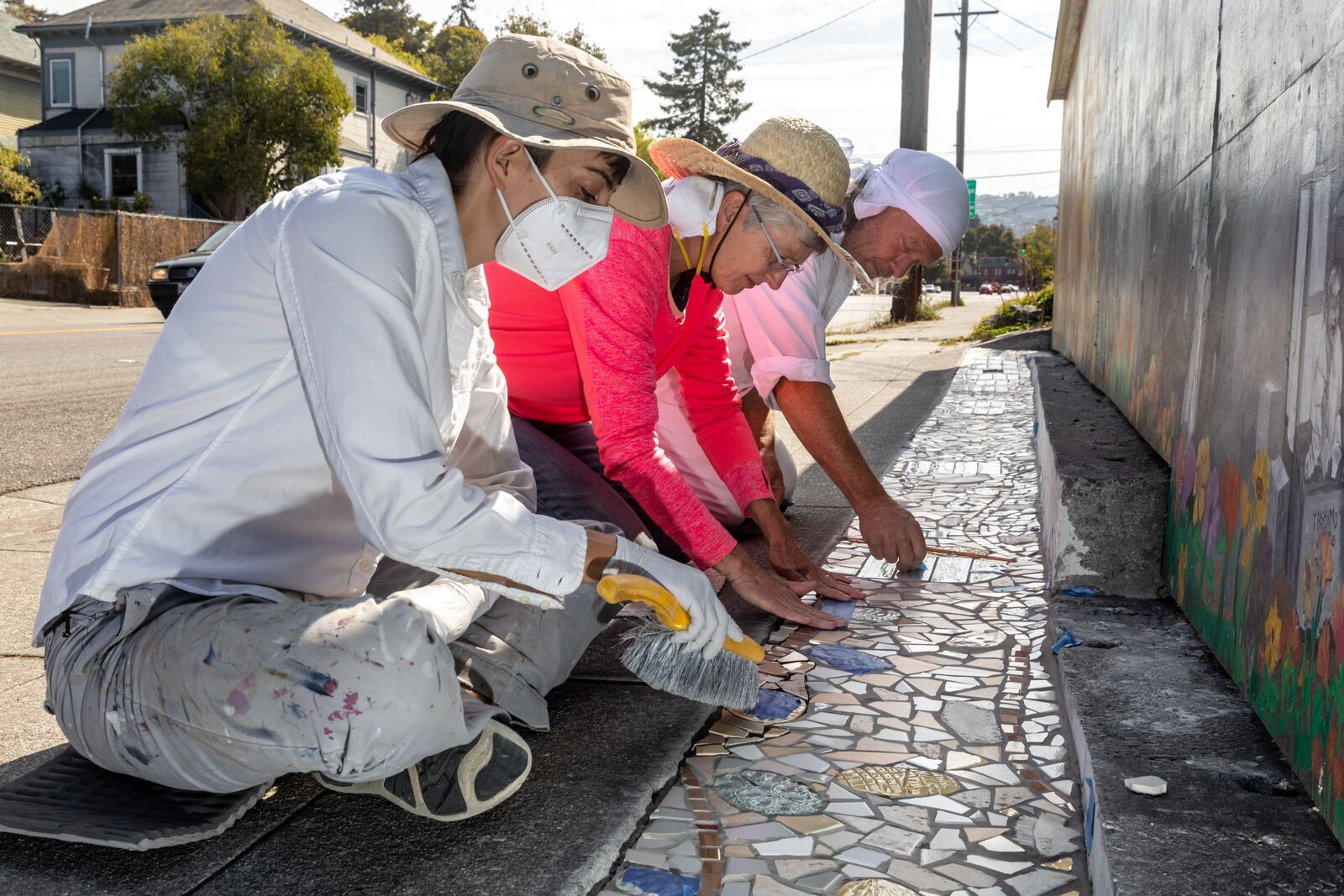 Skip Kirk, Priscilla Hine, and Billy work on the mosaic project on Ashby at Ellis on July 28, 2021. Credit: Kelly Sullivan